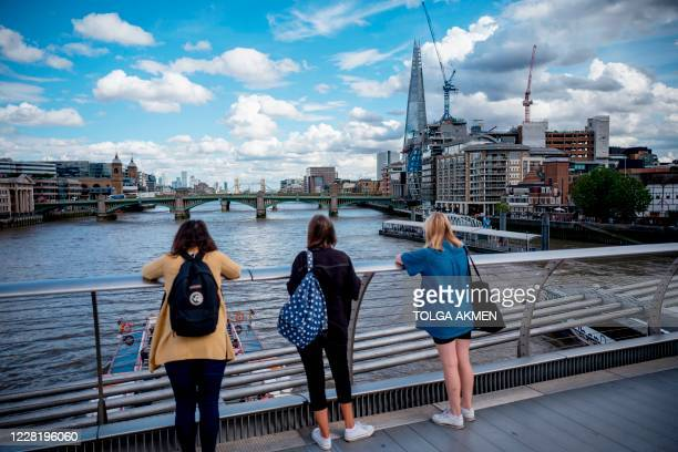 People look enjoy the view of the River Thames from Millennium Bridge in central London on August 24, 2020. - For those tourists who do run the...
