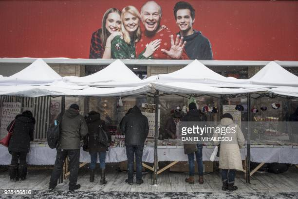 People look for traditional spring charms martisor under makeshift shelters in central Bucharest on February 28 2018 Romanians will be marking March...