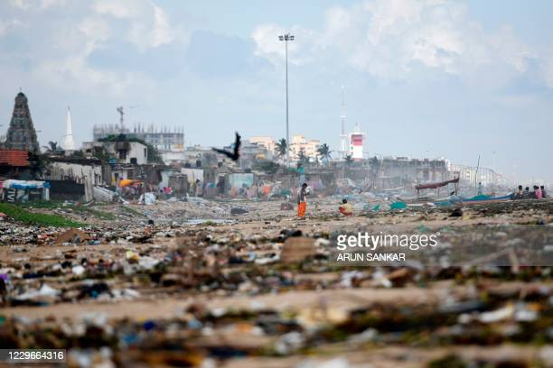 People look for washedup plastic items from a beach after heavy rains in Chennai on November 18 2020