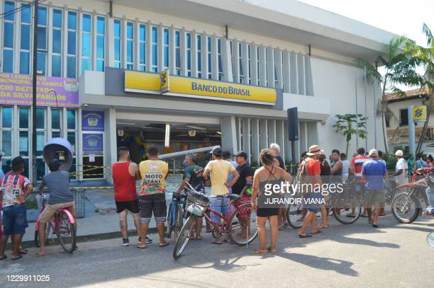 People look into the bank which robbers struck just after midnight, in Cameta, Para State, in northern Brazil, on December 2, 2020. - A hostage was...