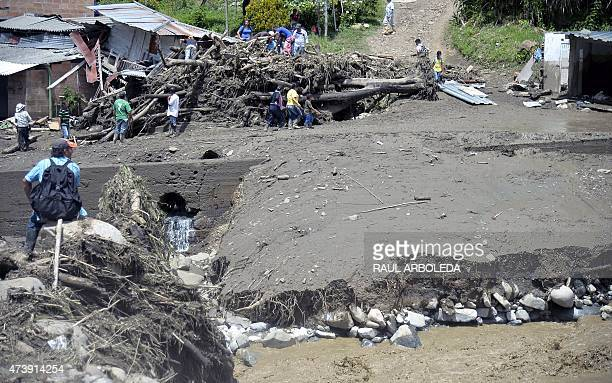 People look into the rubble after a landslide in Salgar municipality Antioquia department Colombia on May 18 2015 A massive landslide tore through a...