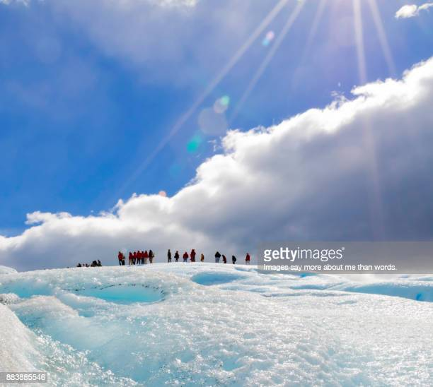 People look like ants as they walk afar by the beauty of the Perito Moreno Glacier.
