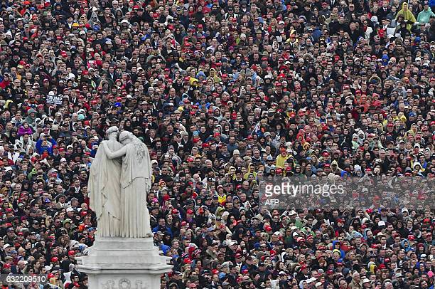 TOPSHOT People look on and listen as US President Donald Trump delivers his inaugural address during the Inauguration on January 20 2017 at the US...