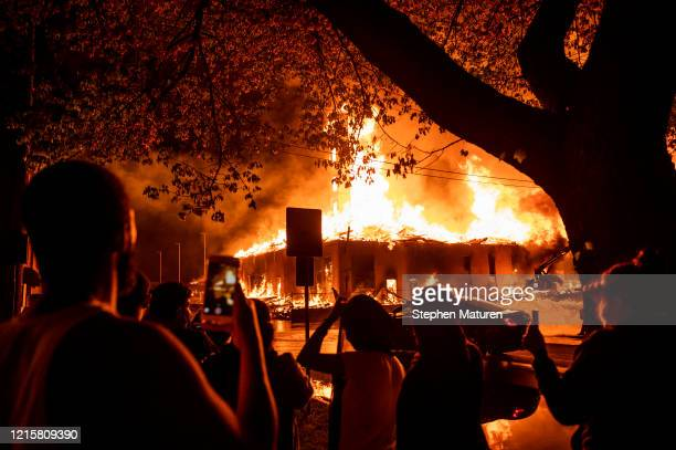 People look on as a construction site burns in a large fire near the Third Police Precinct on May 27 2020 in Minneapolis Minnesota A number of...