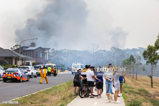 People look on as a fire smoulders at Voyager Point in Western Sydney on January 05 2020 in Sydney Australia One person has died overnight in Batlow...