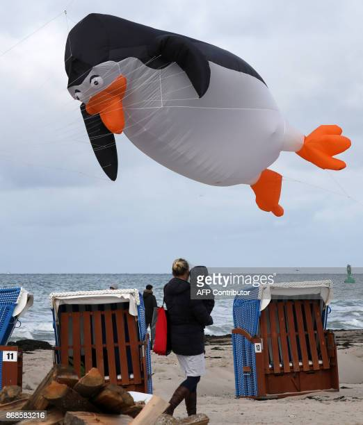 People look on as a giant penguin-shaped kite flutters in the wind over the Baltic Sea beach of Warnemuende near Rostock, northeastern Germany, on...