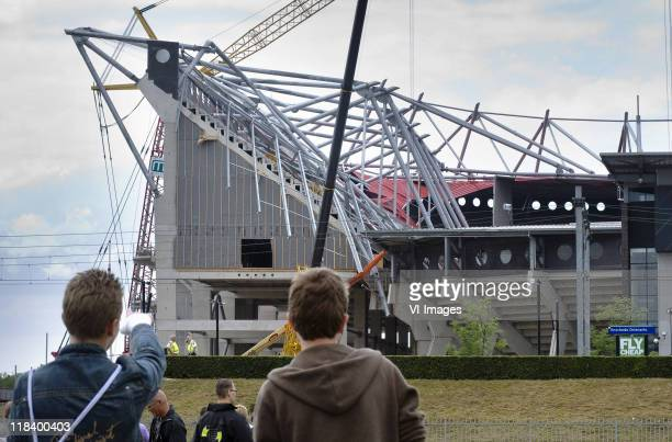 People look on as a rescue operation is under way after part of the roof of De Grolsch Veste Stadium of Dutch club FC Twente collapsed, on July 7,...