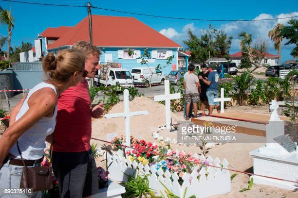 People look on as final preparations are made on December 11 2017 at the cemetery in Lorient on the French Caribbean island of Saint Barthelemy where...