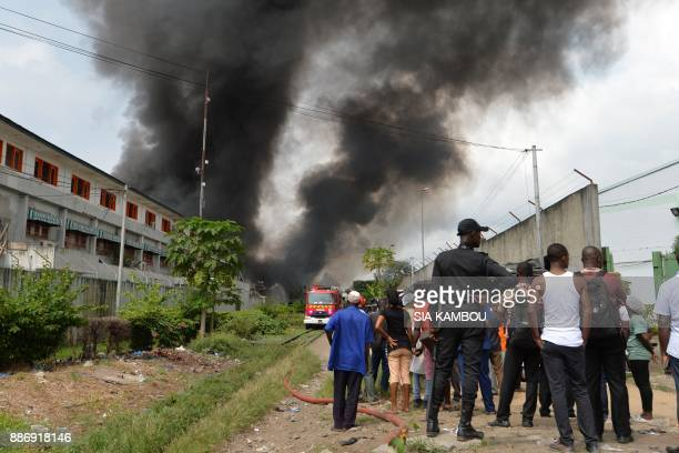 People look on as firefighters battle the remnants of a fire at the Drocolor paint factory on December 6 2017 in Abidjan A huge fire ripped through a...