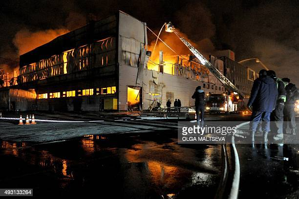 People look on as firefighters work to extinguish a fire at a warehouse of car spare parts in St Petersburg on October 17 2015 AFP PHOTO / OLGA...