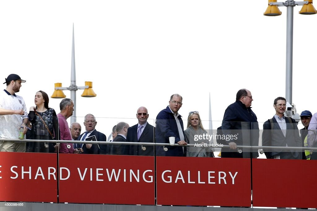 People look on as firemen work in the area as people evacuate The Shard on June 5, 2014 in London, England. The Shard, London's tallest building standing at 310 meters high, was surrounded by fire brigade who evacuated 900 people after smoke was reported in the basement.