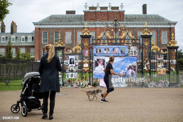 People look on as floral tributes photographs and messages sit outside an entrance gate to Kensington Palace ahead of the 20th anniversary of the...