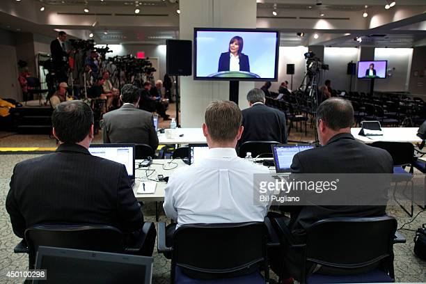 People look on as General Motors Chief Executive Officer Mary Barra is shown on a screen in the press room speaking to employees before holding a...