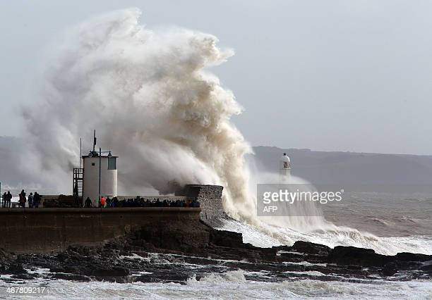 People look on as high waves strike the harbour wall at Porthcawl south Wales on February 8 2014 Strong winds and heavy rain continue to lash the...