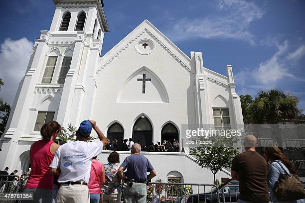 People look on as mourners file into the funeral of Cynthia Hurd at the Emanuel African Methodist Episcopal Church where she was killed along with...