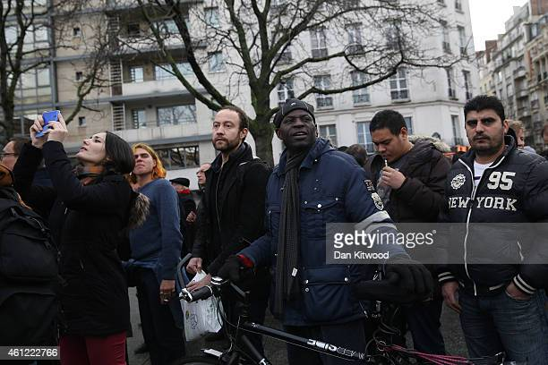 People look on as police mobilize with reports of a hostage situation at Port de Vincennes on January 9 2015 in Paris France According to reports at...