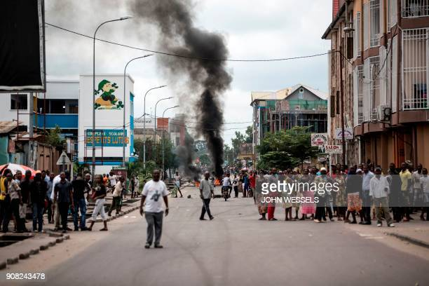 TOPSHOT People look on as protesters burn tyres during a demonstration calling for the President of the Democratic Republic of the Congo to step down...