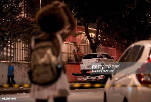 People look on as Rio's Civil Police transport Brazilian politician Marielle Franco's car where she was found shot dead in Rio de Janeiro Brazil on...