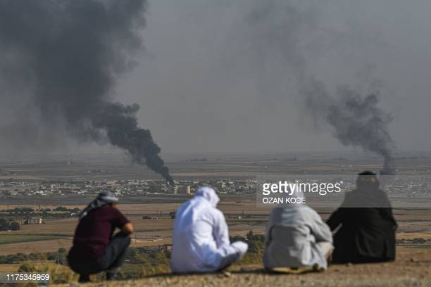 People look on as smoke rises from the Syrian town of Ras al-Ain, in a picture taken from the Turkish side of the border in Ceylanpinar on October 11...