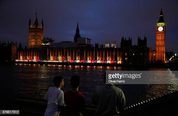 People look on as the blue white and red colours of the French national flag are projected onto the Palace of Westminster the day after the terror...
