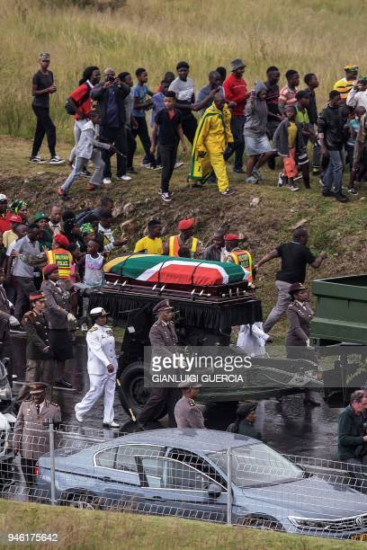 People look on as the coffin of the antiapartheid strongwoman Winnie MandizikelaMandela draped with the South African flag makes it way through the...