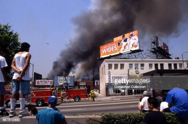 People look on as the LA Fire Department attempts to put out a fire at 307 S Vermont Ave in widespread riots that erupted after the acquittal of 4...