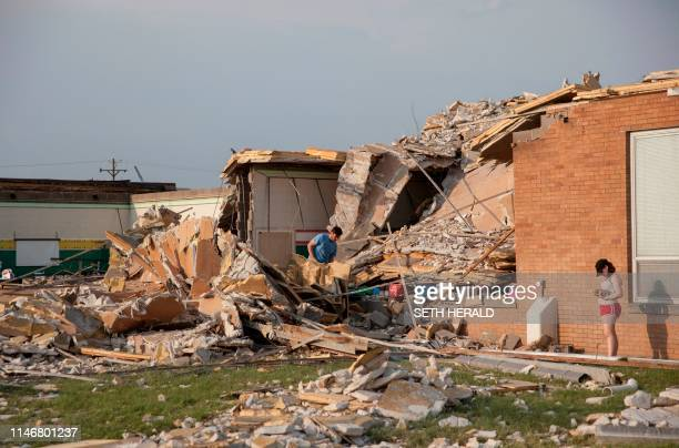 People look on as they examine the damaged remains of school in Dayton Ohio on May 28 after powerful tornadoes ripped through the US state overnight...