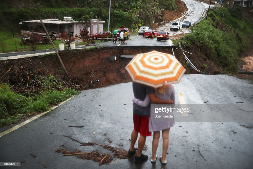 People look on at a section of a road that collapsed and continues to erode days after Hurricane Maria swept through the island on October 7, 2017 in Barranquitas, Puerto Rico. Puerto Rico experienced widespread damage including most of the electrical, gas and water grid as well as agriculture after Hurricane Maria, a category 4 hurricane, passed through.