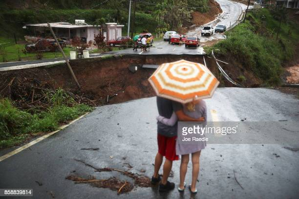 People look on at a section of a road that collapsed and continues to erode days after Hurricane Maria swept through the island on October 7, 2017 in...