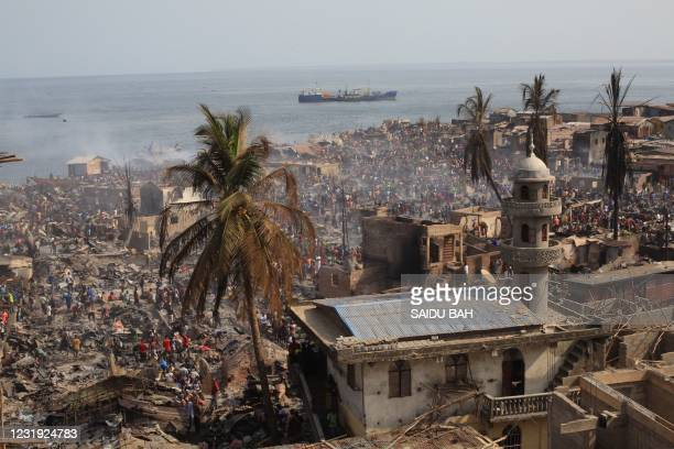 People look on at the aftermath of a large fire that broke out in an informal settlement in Susans Bay, Freetown on March 25, 2021. The fire burned...