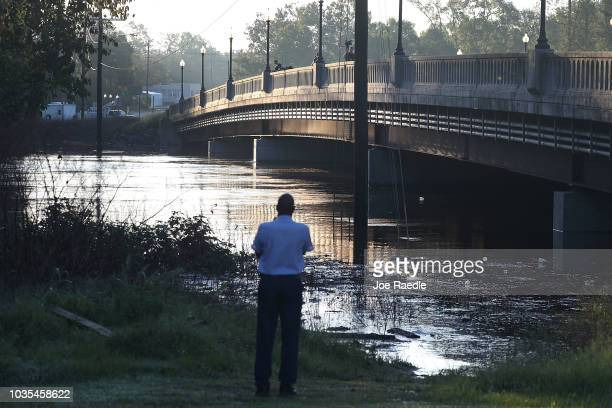 People look on at the Cape Fear river as it crests from the rains caused by Hurricane Florence as it passed through the area on September 18, 2018 in...
