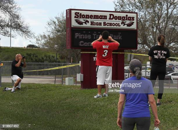 People look on at the Marjory Stoneman Douglas High School on February 18 2018 in Parkland Florida Police arrested 19 year old former student Nikolas...