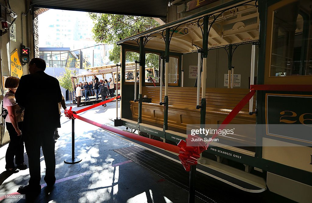People look on from a passing San Francisco Cable Car as officials prepare for a ribbon cutting for newly restored Cable Car #26 during a service inauguration ceremony on November 14, 2012 in San Francisco, California. A service inauguration ceremony kicked off a new life for San Francisco Cable Car #26 that was originally built in 1890 and has been fully restored by hand and put back in service on the streets of San Francisco.