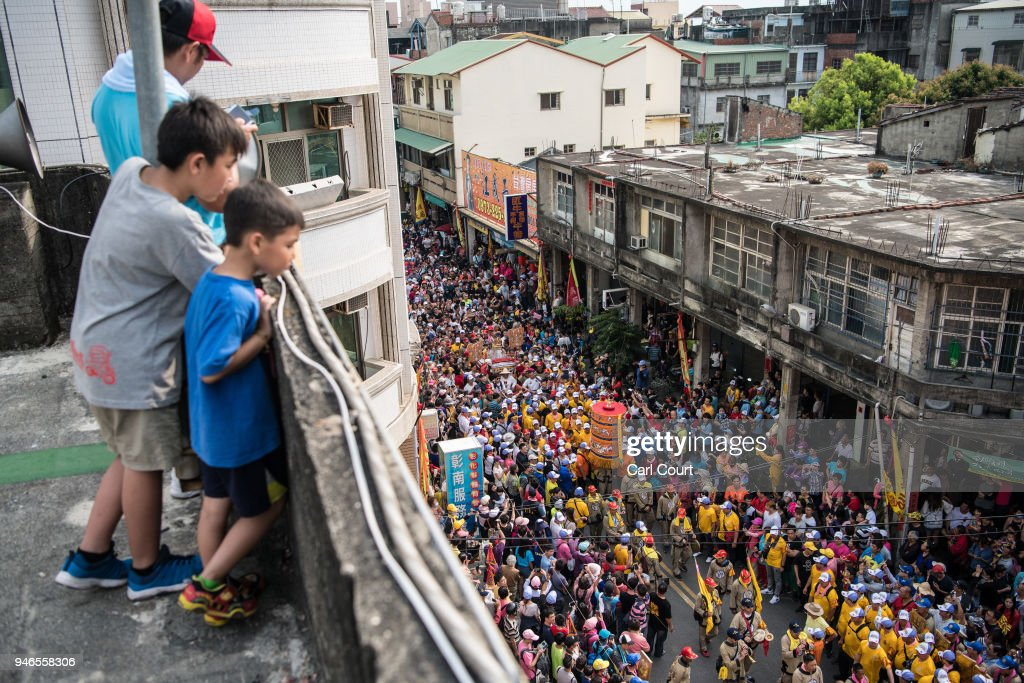 People look on from a rooftop as pilgrims carry a sedan chair holding a statue of the goddess Mazu as they arrive at Houtian Temple on day three of the nine day Mazu pilgrimage on April 15, 2018 in Xizhou, Taiwan. The annual Mazu Pilgrimage begins at Jenn Lann Temple in Taichung and sees around 200,000 pilgrims walk up to 12 hours each day for nine days carrying a statue of Chinese sea goddess Mazu in a sedan chair. The journey covers around 350 kilometres, much of it through mountainous and rugged terrain and visits more than 100 temples before returning to Taichung. The centuries-old pilgrimage is now recognised by UNESCO as living heritage and with an estimated 5 million participants spread over the nine days, it is considered to be one of the greatest religious festivals in the world.