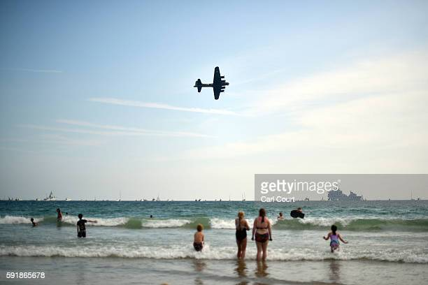 People look on from the beach as a Boeing B17 Flying Fortress flies past during the Bournemouth Air Festival on August 18 2016 in Bournemouth England...