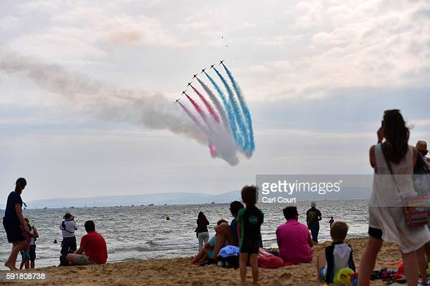People look on from the beach as the Red Arrows aerobatics display team perform during the Bournemouth Air Festival on August 18 2016 in Bournemouth...
