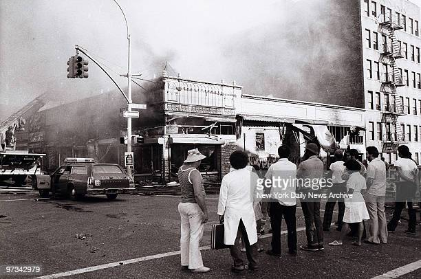 People look on on as firemen put an end to arsonist's handiwork on Marmion Ave in Brooklyn during the aftermath of the blackout of 1977