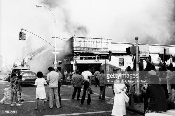 People look on on as firemen put an end to arsonist's handiwork on Marmion Ave in Brooklyn during the aftermath of the 1977 blackout power failure