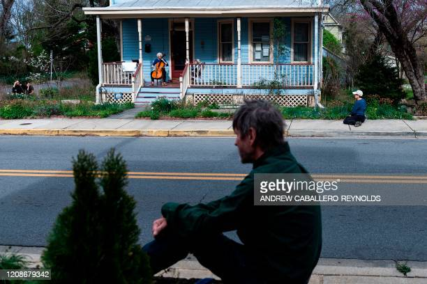 TOPSHOT People look on while practicing social distancing as they watch cellist Jodi Beder perform a daily concert on her front porch in Mount...