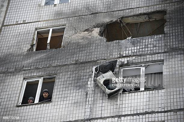 People look out a window on December 1 2014 after their building was shelled during the in the Telstilshik district of the eastern Ukrainian city of...
