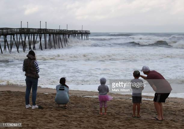 People look out at the Avalon Pier that was damaged by Hurricane Dorian on September 6, 2019 in Kill Devil Hills, North Carolina. Dorian passed...