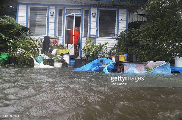 People look out at the flooded street in front of their home as Hurricane Matthew passes through the area on October 7 2016 in St Augustine Florida...