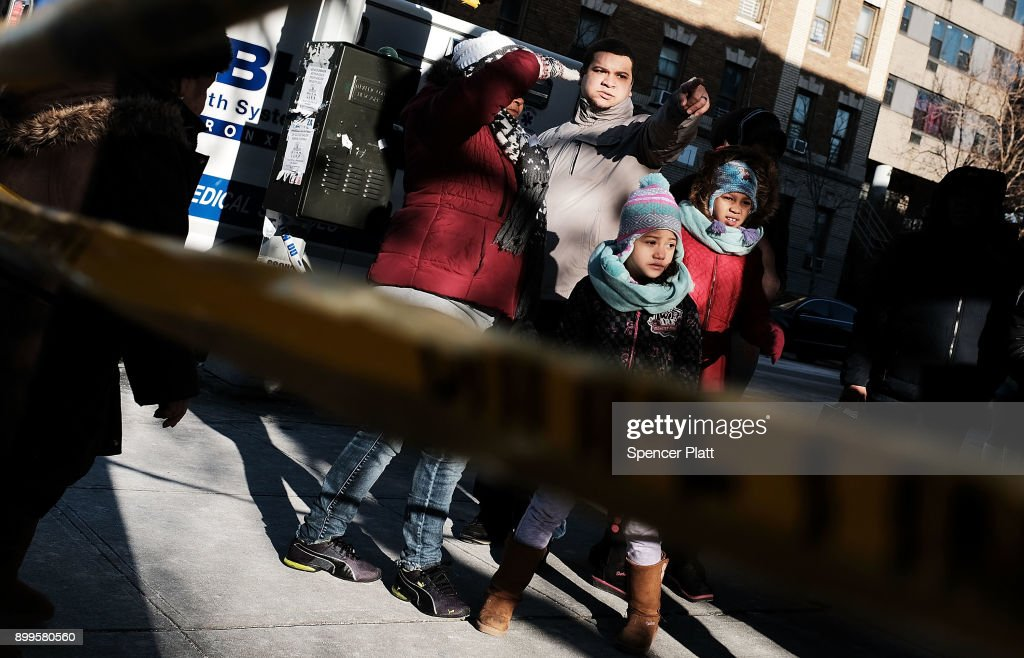 People look out at the scene of a deadly in the Bronx on December 29, 2017 in New York City. At least 12 people, including at least four children were killed in the early evening blaze which officials believe was started by a child playing with the stove.