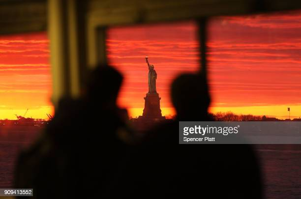 People look out at the Statue of Liberty from the Staten Island Ferry as it stands in New York Harbor at sunset on January 23, 2018 in New York City....