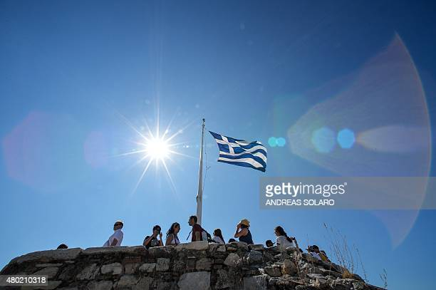 People look out from Acropolis hill in downtown Athens on July 8 2015 Greece's government on July 8 sharply denied a newspaper report that it was...