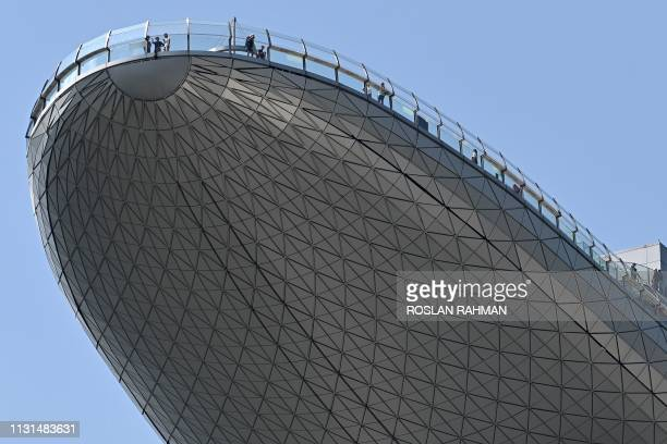 TOPSHOT People look out from the observation deck of the Sands SkyPark at the Marina Bays Sands hotel and resort in Singapore on March 19 2019 Paris...