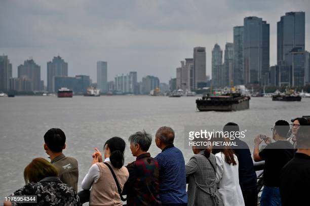 People look out from the promenade on the Bund along the Huangpu River in Shanghai on October 14, 2019