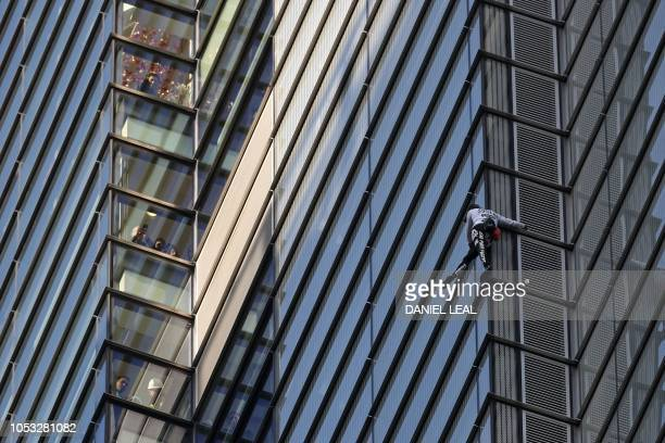 TOPSHOT People look out of nearby windows as French urban climber Alain Robert also known as 'SpiderMan' climbs Heron Tower 110 Bishopsgate in...