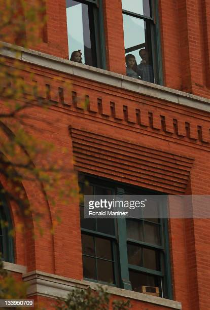 People look out of the seventh floor window of the former Texas School Book Depository now the Dallas County Administration Building on the 48th...