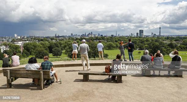People look out over the skyline of London at landmarks including the BT Tower the London Eye and the Shard from Primrose Hill in north London on...
